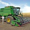 This combine is no longer being used but it is left in for reference.  I am standing alongside a John Deere Model 9600 Hillside Combine which gives a reference to the size of these machines.  It harvests a 30 foot cut and contains a customized automatic levelling device that maintains the central body in a level state while harvesting sidehills holding up to a 37 degree slope.  This provides the proper threshing and cleaning of the crop while the header conforms to the ground slopes.  The central body of the combine including the huge front wheels span 20 feet and with the header on it is 30 feet wide.  The combine weighs empty about 34.000 pounds and a full bulk tank holding 300 bushels of wheat adds another 18,000 pounds for a grand total of 51,000 pounds or over 25 tons gross weight! It is powered by a supercharged 330 HP Diesel engine coupled with a hydraulic transmission drive system providing an infinite selection of ground speeds.  Note the fully enclosed  air-conditioned operator cab.  The harvest will usually last about a month.  Although wheat is the dominant crop in the area, these combines also harvest dry peas as some of the photos will show.