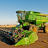 This is the new addition replacing the old John Deere 9600.  The John Deere 9860 STS with Acculevel Levelling System levels to 35 degree grades.  With the 35 foot cut header the combine weighs approximately 50,000 pounds.  A 360 HP Diesel engine supplies power.  The 26 foot unloading auger swings out for unloading on the go.  An infinite hydraulic drive system powers all wheels.  The operator is provided with a vast array of electronics that automatically control the function of header height, reel speed, and the multiple threshing and cleaning settings thus relieving the operatior of much of  these constant needs    It leaves him  to monitor, drive and control speed in all varying conditions.. The electronics  also provide vital information on the performance of the threshing and cleaning systems.  The bulk tank holds 300 bushels which will add another 18,000 pounds for a total of approximately 68,000 pounds.  With all this weight at 34 tons, it needs the large dual wheels on the main axle plus the large rear axle wheel  and four wheel drive  to provide safe harvesting on the steep hillsides.