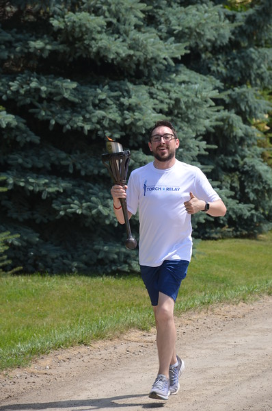 Phil Kraft,  a member of the Macomb County Board of Commissioners from District 8, finishes his leg of the Bicentennial Torch Relay.