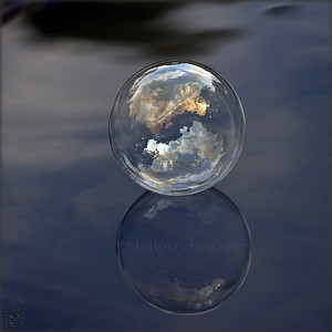 A bubble reflecting sunset and floatting on a river.