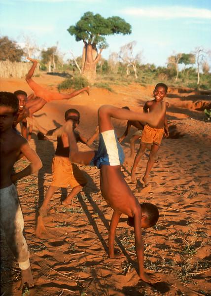 Boys doing backflips with baobab in background, Ifaty, Madagascar