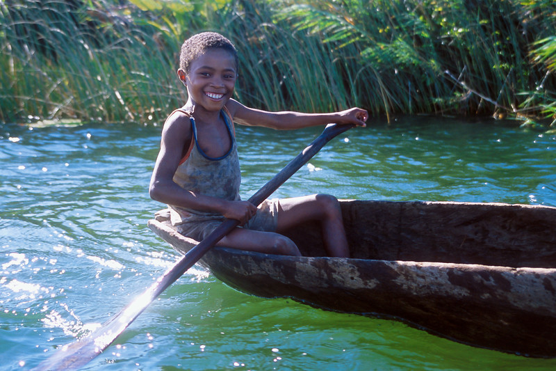 Boy paddles pirogue in Pangalanes Canal, Madagascar