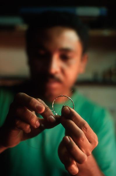 """Miniature Mamy"" creates miniature bicycle wheel, Antsirabe, Madagascar."