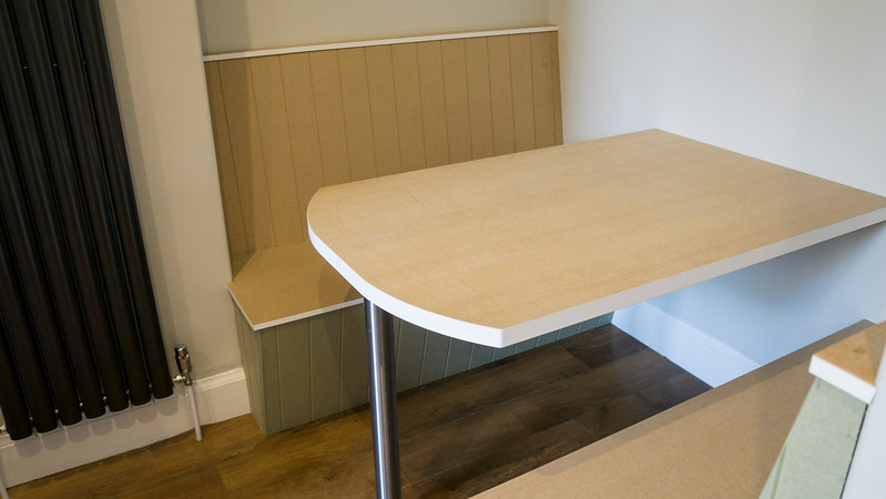 Booth Style seating and table awaiting hand paint finish and glass table top.