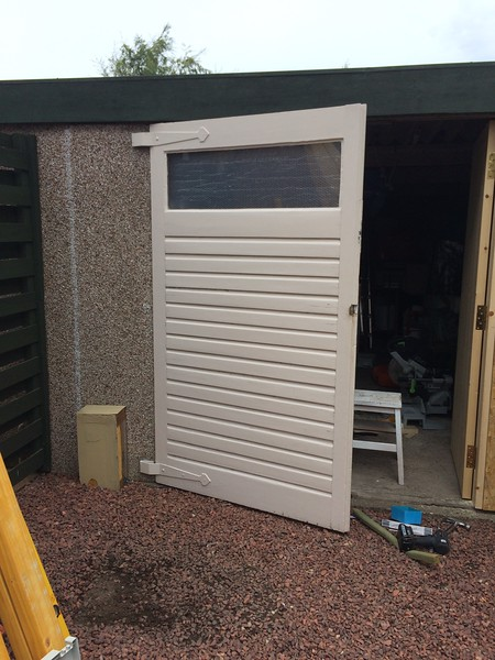 Old double doors removed and replaced with single door and siding