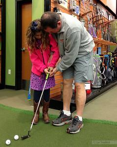 Papa teaching her to putt