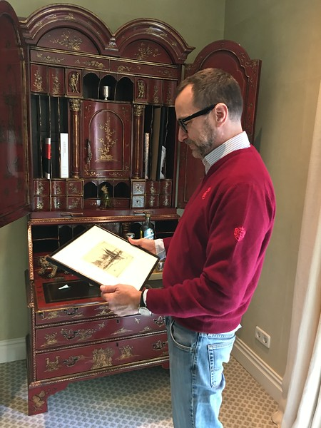 Ambassador James Costos looking at a Whistler etching gifted to him