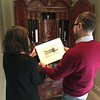 Sara Bogosian and Ambassador James Costos looking at a Whistler etching gifted to him