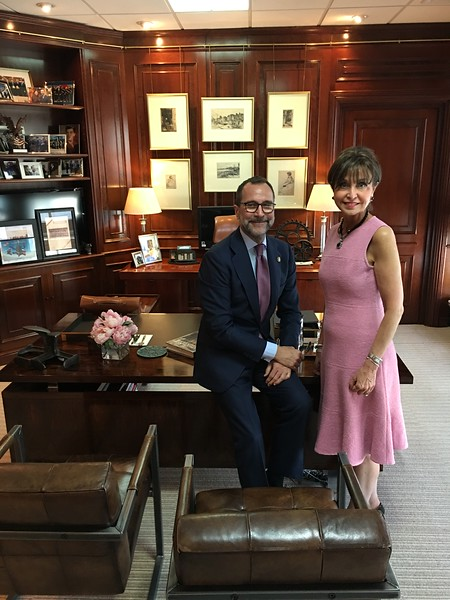 Ambassador James Costos and Sara Bogosian in front of the borrowed Whistler etchings in his embassy office.