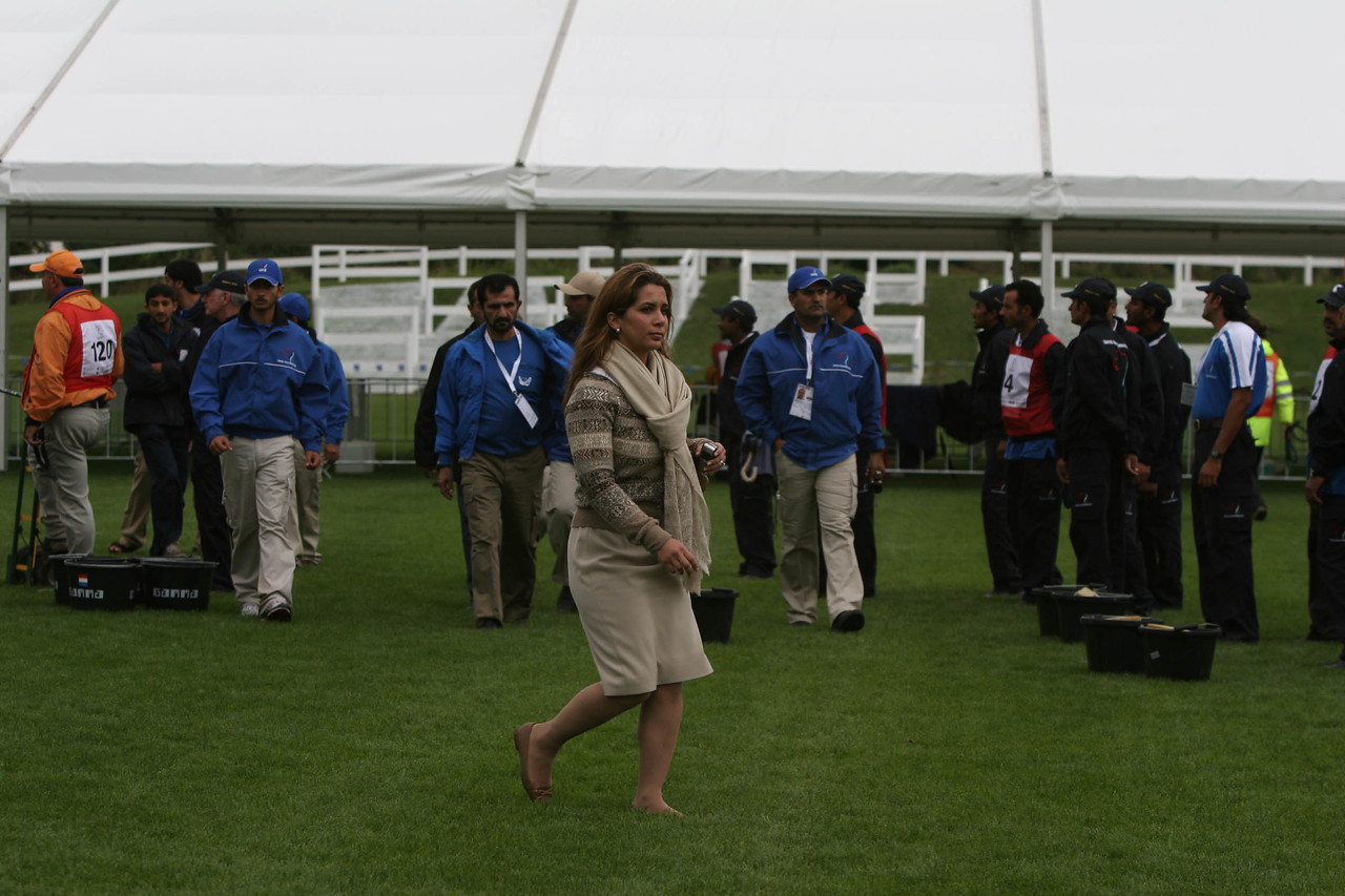 #21- Candid: Princess Haya walks from 5th Vet gate.  Sh. Mohammed (husband) in background.