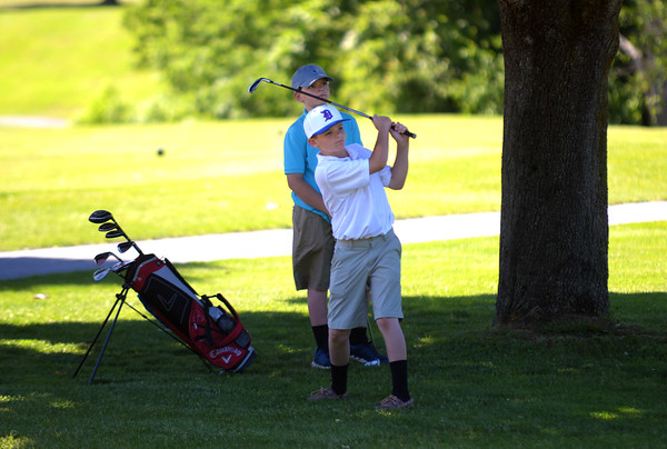 JIM VAIKNORAS/Staff photo Peyton Pallidino, 12, hits a shot just off the 18th green with his brother Brett 14 behind him at  Beverly Golf and Tennis. The brothers are from Danvers and are members of the club.