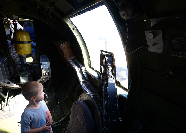 JIM VAIKNORAS/Staff photo Thomas Carlin, 3, of Ipswich looks out the side gunner window of a B 17  during the Collins Foundation Wings of Victory Tour at Beverly Airport.