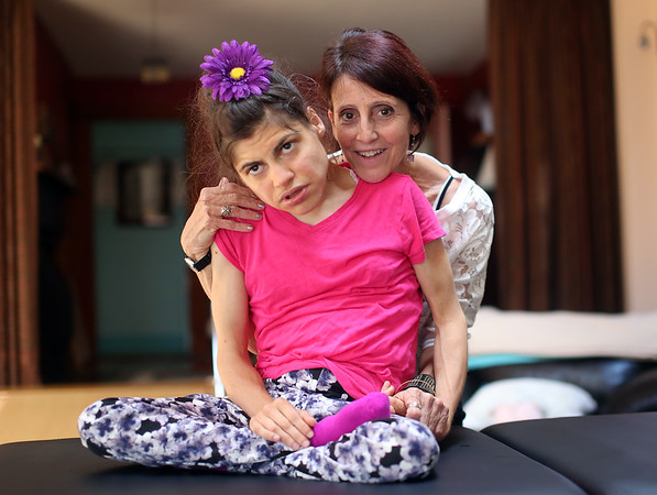 DAVID LE/Staff photo. Carol Amore, of Beverly, takes care of her daughter Sarah Carr, daily since she had her first seizure at the age of five. 8/18/16.