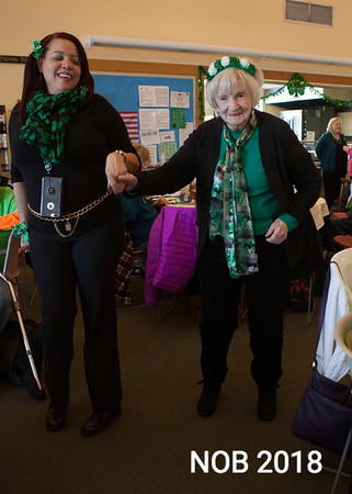 AMY SWEENEY/Staff photo. Bibian Maria, left, helps Evelyn Harrington to the dance floor during the St. Patrick's Day party at the Beverly Senior Center. 3.15.2018
