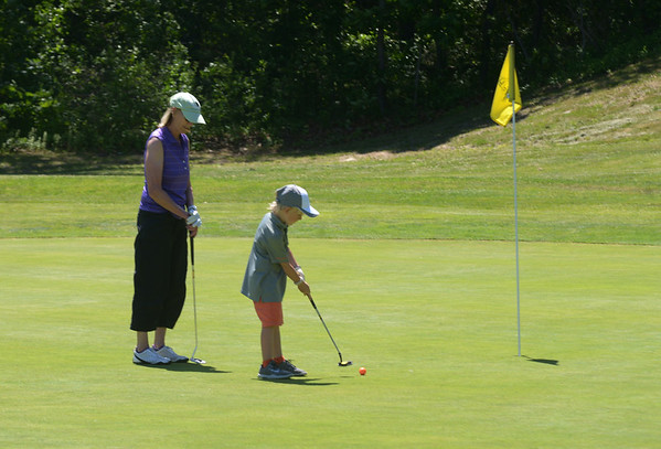 JIM VAIKNORAS/Staff photo Bryson Preacher 6, makes a putt on the 1st green at Beverly Golf and Tennis while playing with his grandmother Sallie Larkford.