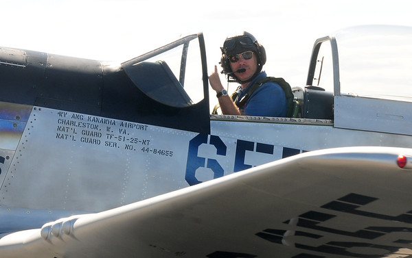 JIM VAIKNORAS/Staff photo Rob Collins fsignals as he takes off in a P 51 Mustang during the Collins Foundation Wings of Victory Tour at Beverly Airport. The WW2 era fighter plane was often used as a bomber escort and has a top speed of over 400MPH.