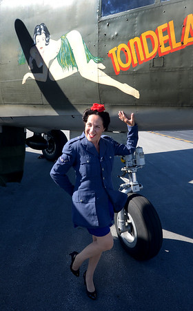 JIM VAIKNORAS/Staff photo Catherine Chiusano of Beverly dressed in a vintage Air Force jacket and put her hair in a victory roll as she poses with the nose of a B-25 Mitchell bomber during the Collins Foundation Wings of Victory Tour at Beverly Airport.