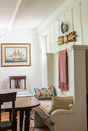 The former church pew is one of the first pieces of furniture the couple bought for the house. The carved double-ended cedar pineapple with gold leaf on the wall belonged to Susan's mother and was carved by a man from Nahant.