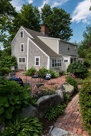 The side of the Sarah and Ben Anderson's Putnam Lane home features perennial gardens, stone walls and a brick patio that the couple built themselves.