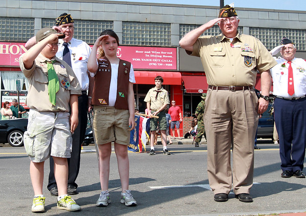 From left, Danvers Boy Scout Mike Shannon, Mark McDermott, Danvers Girl Scout Braiden Devitt, Commander Dick Moody, and Steve Godzik, salute a wreath they just placed in Danvers Square during the Memorial Day Parade on Monday. David Le/Staff Photo