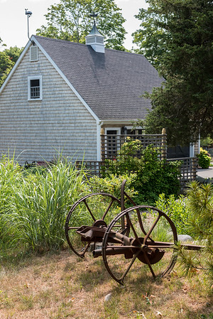 "The couple built the two-car garage with its handsome cupola, adorned with a grasshopper weathervane. The old plow was on the property when they arrived. ""It's not original but we decided to keep it,"" says Susan. ""Every house becomes what it is over time."""
