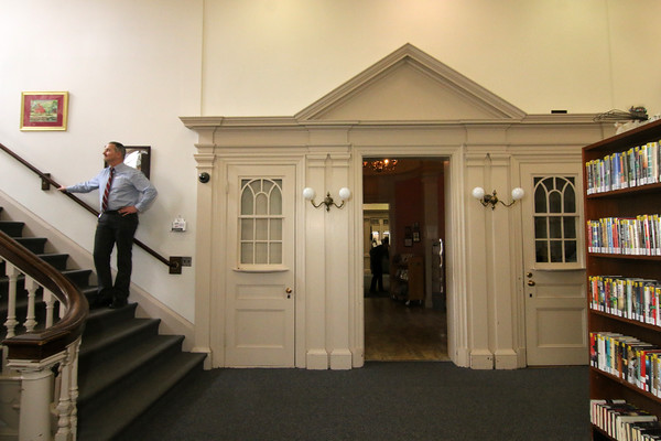 Photo by Allegra Boverman. At the Peabody Institute Library of Danvers with Library Director Alan Thibeault in front of what used to be the entrance to the building's auditorium. At left of the entranceway would have been a ticket window, now a private bathroom for his office. At right was a phone room.
