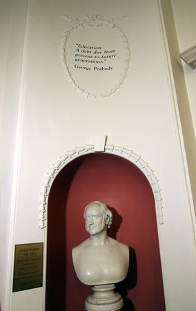 "Photo by Allegra Boverman. A bust of George Peabody, whom the Peabody Institute Library is named is in the main lobby with the quote ""education is a debt due from present to future generations"" placed above it."