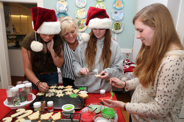 AMY SWEENEY/Staff photo<br /> Terry Cawlina, second from left, checks to see how the decorating is going her daughter and friends: Carolyn Larsen, 16, left, her daughter Sophie Cawlina, 19, and Alena Larsen, 19, decorate Christmas cookies at the Cawlina home in Danvers.<br />  10/9/16