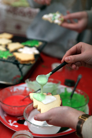 AMY SWEENEY/Staff photo<br /> Alena Larsen, 19, ices a sugar cookie cut like a Christmas tree.