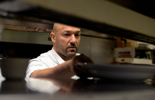 RYAN HUTTON/ Staff photo<br /> Essex Street Grill owner Carl Pervanas puts up a dish of seafood fra diabolo to order in the kitchen of his restaurant.