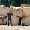 Pat Christman<br /> Mankato Kasota Stone's Brett Skilbred walks past blocks of Kasota stone stored at one of the company's quarries in Mankato. The largely unseen quarries in Mankato have closed as the recession-driven slowdown in construction hurt the market for local limestone.