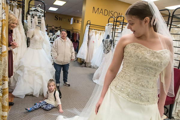 """Zoiey Grewe (bottom left), 5, looks at her sister Heather Grewe who was trying on wedding dresses at Encore Consignment and Bridal Boutique with the help of employee Carroll Meyers-Doblers (left) and Amy Grewe. """"She's beautiful,"""" Zoiey said repeatedly as Heather tried on dresses. Photo by Jackson Forderer"""
