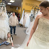"Zoiey Grewe (bottom left), 5, looks at her sister Heather Grewe who was trying on wedding dresses at Encore Consignment and Bridal Boutique with the help of employee Carroll Meyers-Doblers (left) and Amy Grewe. ""She's beautiful,"" Zoiey said repeatedly as Heather tried on dresses. Photo by Jackson Forderer"