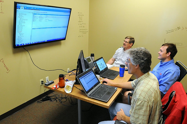 From left, Tom Uehling, Titus Kennedy and Tim Cherney work in a small conference room. The walls are painted with a special paint that allows them to act as a dry erase board. Photo by Pat Christman