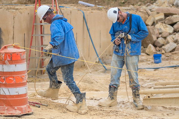 Tom West (left) and Joe Vetter work on setting up a wire saw at the Vetter Stone quarry. Photo by Jackson Forderer