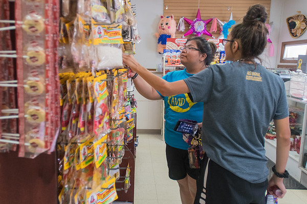 Yadira Mendez (middle) and Anahi Mendez (right), 11, look for candy to buy at Jalisco Market. The store sells Hispanic foods and other Hispanic-oriented products.