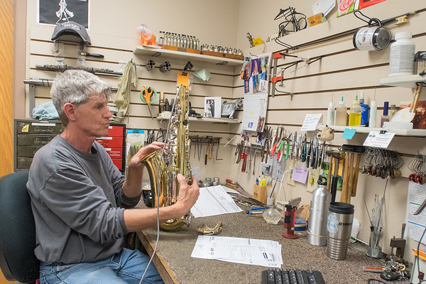 Dan Robinson uses a leak light to check for leaks in a saxophone at Music Mart. Music Mart fixes and sells instruments, as well as having music lessons. Photo by Jackson Forderer