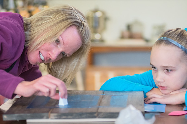 Beth Hinrichson (left) dabs a stencil on a piece of wood during a class at Design and Wine while her daughter Kara Hinrichson, 9, looks on. Photo by Jackson Forderer