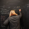 Joy Boertje, manager at Sweet Alice's Floral and Art, writes a note on a giant employee chalkboard in the store in St. Peter.