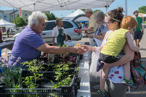 Sue Musser (left) gives change back to customer Emily Champon at the farmers market held every Saturday at the Best Buy parking lot. Musser, from Fairmont, has been a vendor at the farmers market for over 30 years. Photo by Jackson Forderer