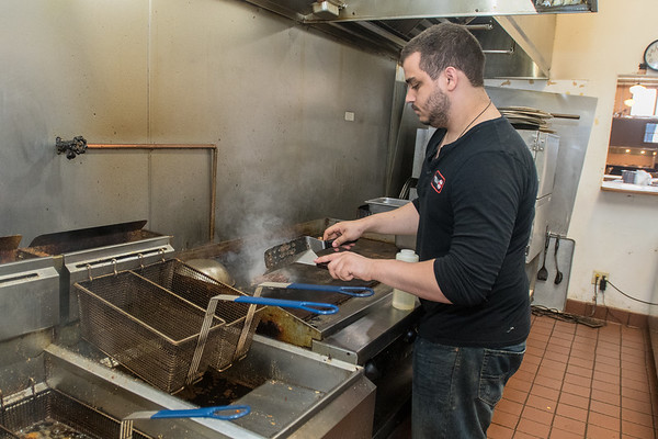 Damion Taylor cooks a hamburger in the kitchen at the Henderson Road Haus Eatery. Photo by Jackson Forderer