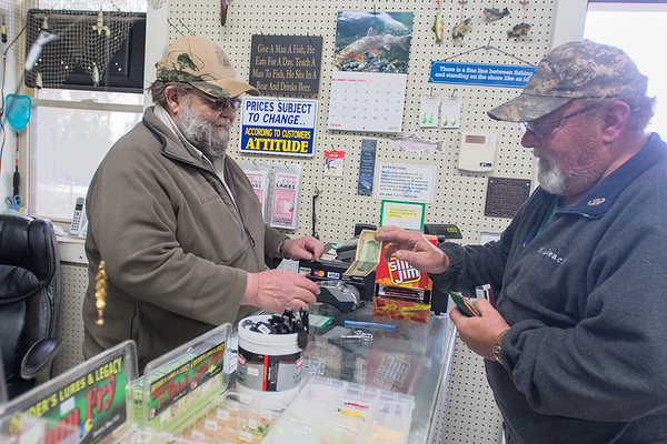 Walt Hohn (left) takes cash for Joe Lindgren's purchase at his bait shop in rural St. Peter. The shop is dotted with fishing humor signs such as, There is a fine line between fishing and standing on the show like an idiot. Photo by Jackson Forderer
