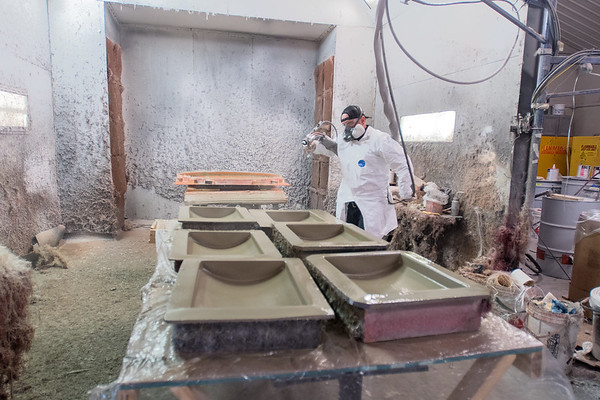 Aaron Cotton with Blackhawk Fiberwerx puts a gel coating on a mold that will be used to make an outdoor fire pit at the business in rural St. James. Photo by Jackson Forderer