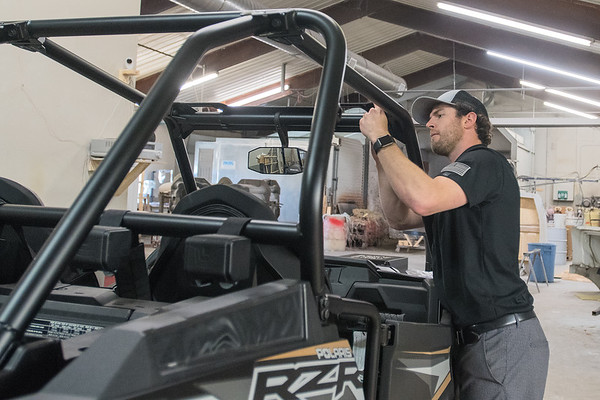 Tyler Deike works on a roof for a Polaris RZR 1000 at Blackhawk Fiberwerx in rural St. James. Deike said he bought the business because he has a manufacturing background and was sick of working his day job and added, I want to do some fun stuff. Photo by Jackson Forderer