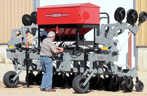 Wayne Buck with a cover crop seeder, an experimental machine they're testing with area farmers. Photo by Pat Christman