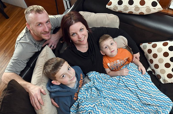 Allie Anderson, her husband Joel, and sons Tate (left), 8, and Ty, 5, with the original prototype Balanced Blanket made for Tate. Photo by Pat Christman