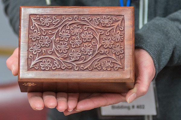 Wendy June of Mankato Pet Cremation holds an intricately carved box that can be used for a pet's ashes. June said her incinerator burns at about 800,000 BTUs, while the average home burns at about 30 BTUs. Photo by Jackson Forderer