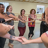 Dancers in a Satori Violet belly dancing class join hands in a circle during a rehearsal in the studio. Photo by Jackson Forderer
