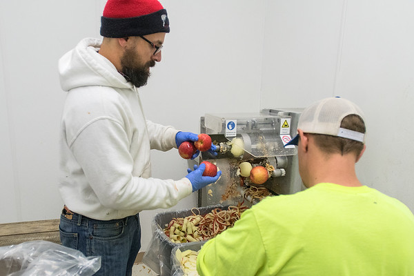 Tim Harbo feeds apples into an apple slicing machine at Welsh Heritage Farms. Rob Menard The machine isn't used for the cider making process, but for apple slices for apple pies. Harbo Hard Cider is an offshoot of Welsh Heritage Farms.  Photo by Jackson Forderer