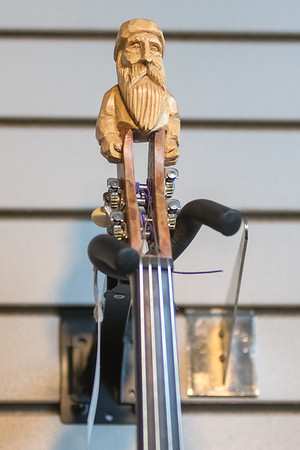 A handmade carving at the end of the neck of a banjo in the Ouren Instruments shop.